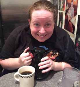 me looking totally overjoyed while holding a carafe, with a full coffee cup in front of me