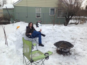 my spouse sitting in a camping chair beside a fire pit in the snow