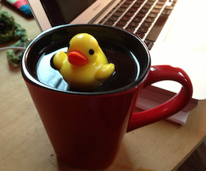 a duck-shaped tea infuser floating on a red mug