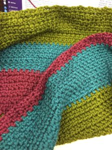 Part of a blanket, crocheted, in purple, blue-green, and green jewel tones