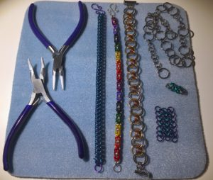 A blue piece of fabric with pliers, three bracelets, and some small hand-made chains on it