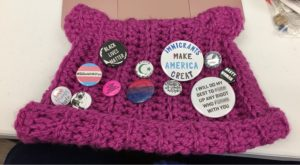 A pink hat with cat ears and a bunch of activist buttons on it