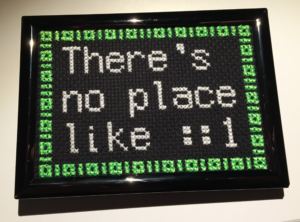 "A finished and framed cross stitch that says ""There's no place like ::1"" with 1s and 0s acting as a decorative border"
