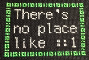 "A cross-stitch that says ""There's no place like ::1"" with 1s and 0s acting as a border"