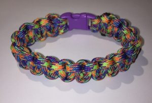 A bracelet made out of brightly colored paracord, with a purple buckle