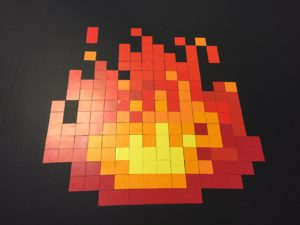 What looks like an 8-bit image of a fire, made with red and yellow squares on a black background